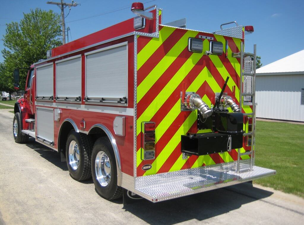 Rear view of an Osco Tank and Truck Sales Dominator fire truck with yellow and red emergency stripes painted in a downward facing chevron pattern. The 2010 Freightliner truck features four roll-up stainless steel access panels.