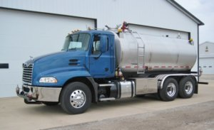 Diesel Exhaust Fluid truck with blue cab and stainless steel tank.